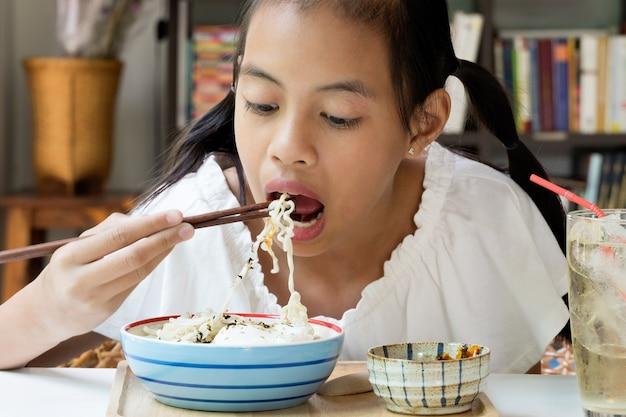 Asiatisches mädchen, das sofortige korea-nudeln isst