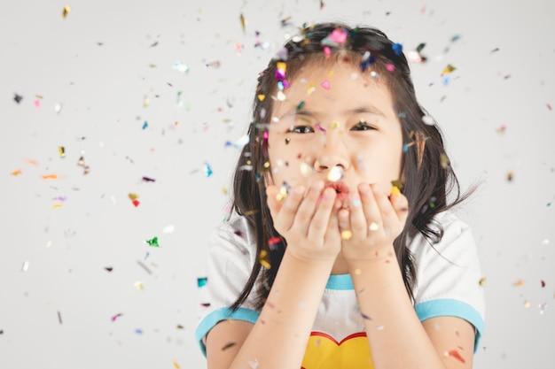 Asiatisches mädchen, das spaß mit bunten konfettis auf grau hat.