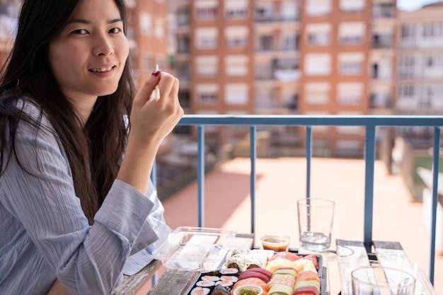 Asiatisches mädchen, das sushi auf dem balkon isst, der auf einem stuhl auf der terrasse in der freizeitkleidung sitzt