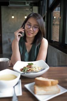 Asiatisches mädchen, das telefon benennt