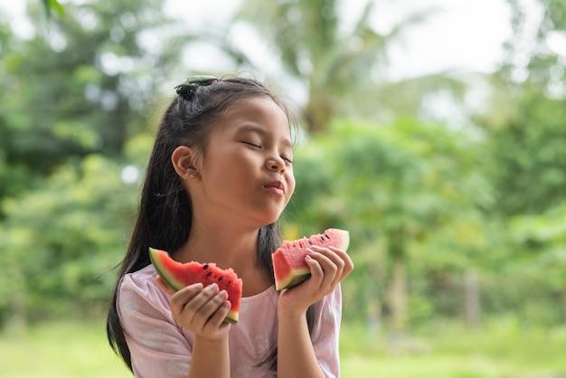 Asiatisches mädchen, das wassermelone isst