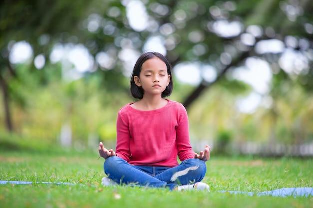 Asiatisches mädchen, das yogahaltung im park im freien tut