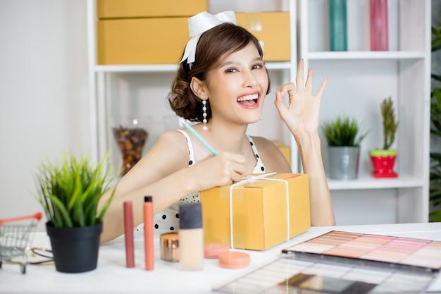 Asiatisches mädchen, das zu hause büro bearbeitet und paketbriefkasten zum zustelldienst zum kunden sortiert