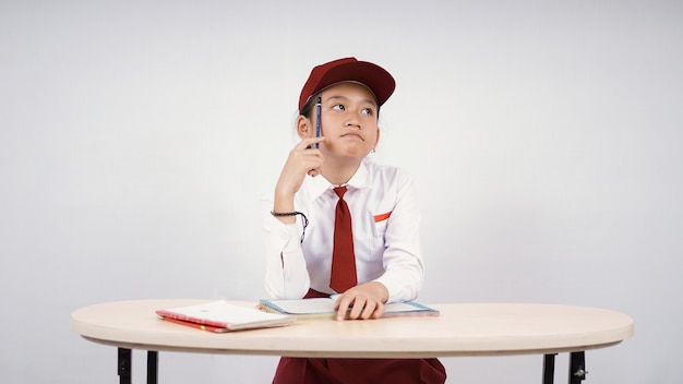 Asiatisches mädchen der grundschule, das an eine idee denkt, isoliert auf weißem hintergrund zu schreiben