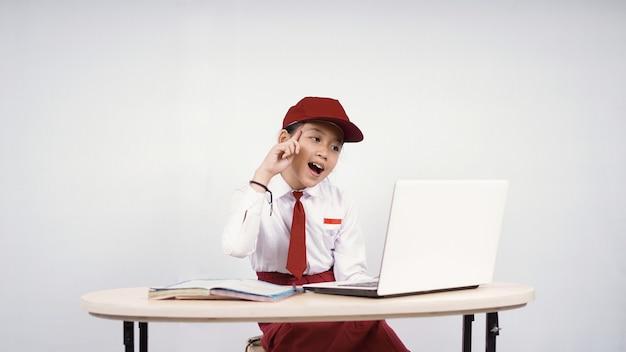 Asiatisches mädchen der grundschule, das an ideen vom laptop-bildschirm denkt, der auf weißem hintergrund lokalisiert wird