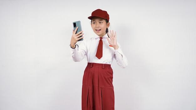Asiatisches mädchen der grundschule, das auf ihrem telefonschirm lokalisiert auf weißem hintergrund winkt