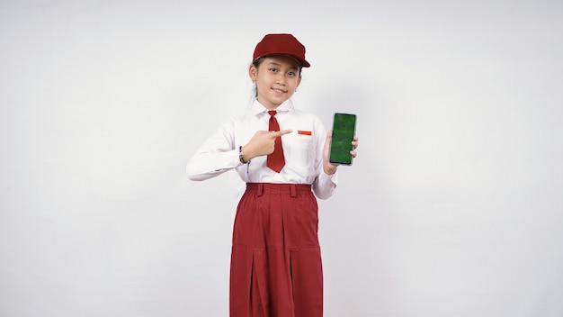 Asiatisches mädchen der grundschule, das auf smartphone-bildschirm zeigt, der auf weißem hintergrund lokalisiert wird