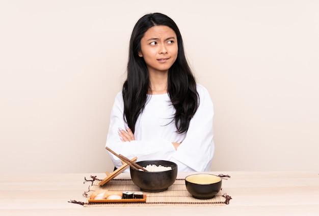 Asiatisches mädchen des asiatischen teenagers, das asiatisches essen lokalisiert auf beige isst