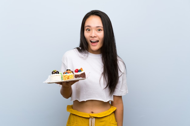 Asiatisches mädchen des jugendlichen, das viele verschiedenen minikuchen mit überraschung und entsetztem gesichtsausdruck hält