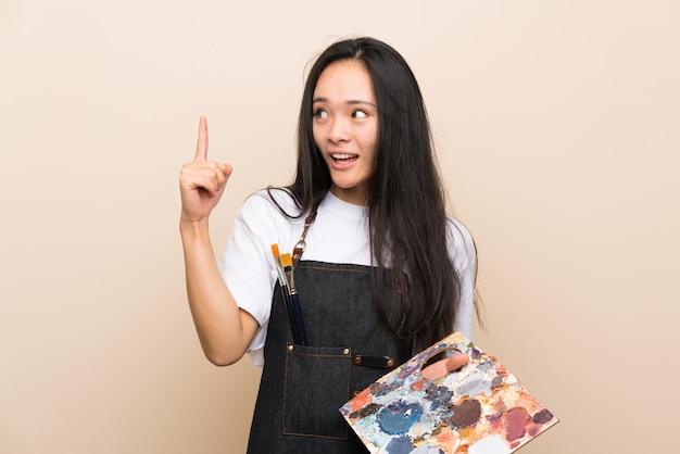 Asiatisches mädchen des jugendlichmalers, das beabsichtigt, die lösung beim anheben eines fingers zu verwirklichen