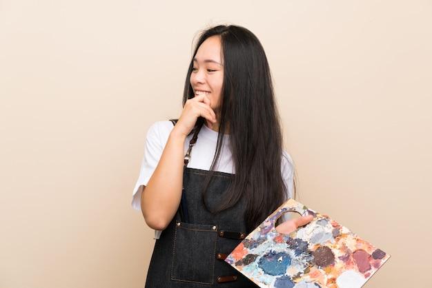 Asiatisches mädchen des jugendlichmalers, das eine idee denkt und seite schaut