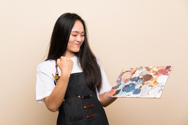 Asiatisches mädchen des jugendlichmalers, das einen sieg feiert