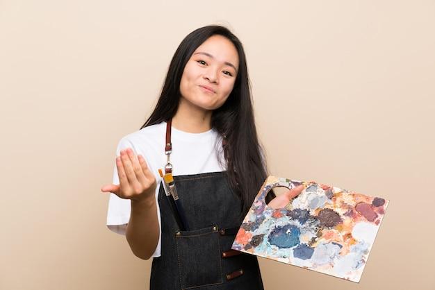 Asiatisches mädchen des jugendlichmalers, das einlädt, mit der hand zu kommen. schön, dass sie gekommen sind