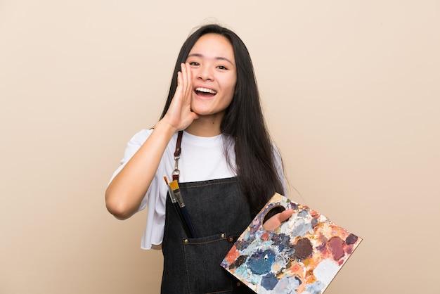 Asiatisches mädchen des jugendlichmalers, das mit dem breiten mund schreit, öffnen sich