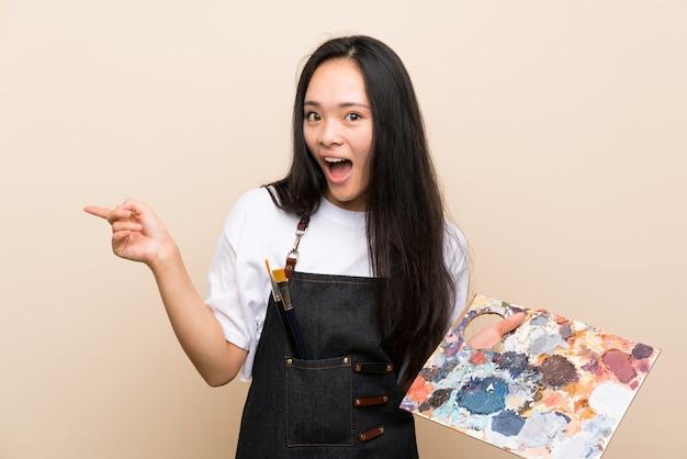 Asiatisches mädchen des jugendlichmalers überrascht und finger auf die seite zeigend