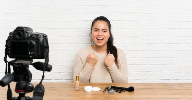 Asiatisches mädchen des jungen bloggers, das ein videotutorium feiert einen sieg notiert