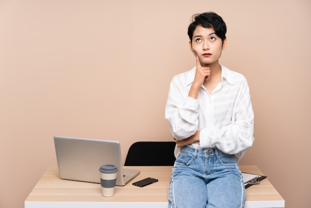 Asiatisches mädchen des jungen geschäfts an ihrem arbeitsplatz eine idee denkend
