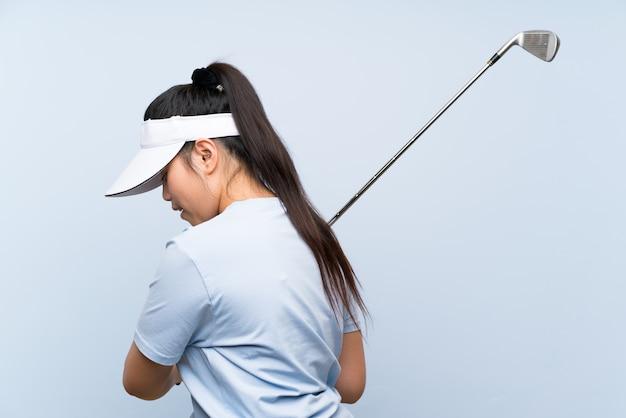 Asiatisches mädchen des jungen golfspielers über lokalisierter blauer wand