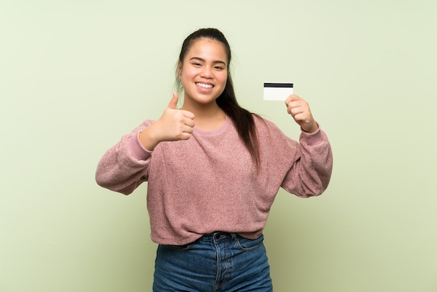 Asiatisches mädchen des jungen jugendlichen über der lokalisierten grünen wand, die eine kreditkarte hält