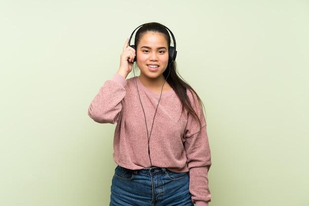 Asiatisches mädchen des jungen jugendlichen über lokalisierter grüner wand hörend musik mit kopfhörern