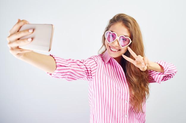 Asiatisches mädchen des jungen lustigen bloggers macht selfie auf der telefonkamera