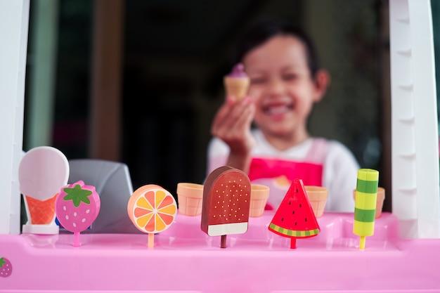 Asiatisches mädchen des lächelns kind, das mit plastikeiscremeshop spielt