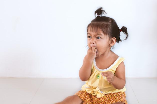 Asiatisches mädchen des netten babys kind, das nudel allein isst und eine verwirrung auf ihrem gesicht und hand macht
