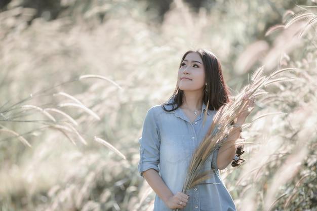 Asiatisches mädchen des portrait-thai-modells mit dem gras, das im garten aufwirft und lächelt