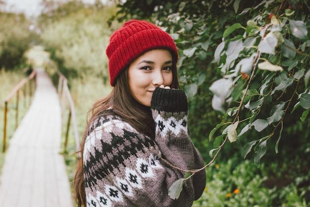 Asiatisches mädchen des schönen sorglosen langen haares im roten hut und in gestrickter nordischer strickjacke im herbstnaturpark, reiseabenteuerlebensstil