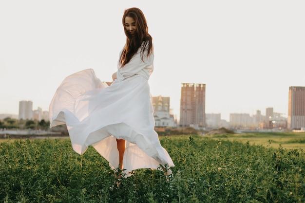 Asiatisches mädchen des schönen sorglosen langen haares in der weißen kleidung und im strohhut genießt das leben auf dem naturgebiet bei sonnenuntergang