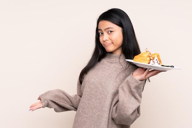 Asiatisches mädchen des teenagers, das waffeln lokalisiert auf beige hält