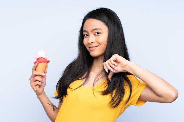 Asiatisches mädchen des teenagers mit einem kornetteis auf blauer wand stolz und selbstzufrieden
