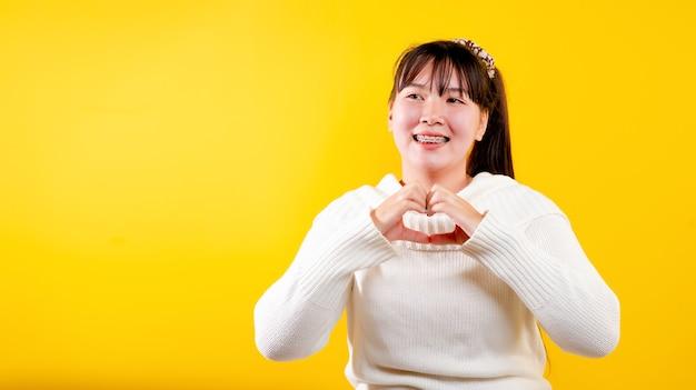 Asiatisches mädchen dieses fröhliche, lustige, strahlende lächeln. ausdruck liebevoller augen gutes leben und glück bei der arbeit, entspannung, vor gelbem hintergrund Premium Fotos