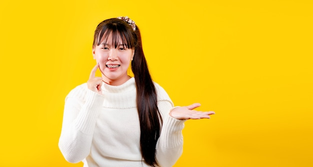 Asiatisches mädchen dieses fröhliche, lustige, strahlende lächeln. ausdruck liebevoller augen gutes leben und glück bei der arbeit, entspannung, vor gelbem hintergrund