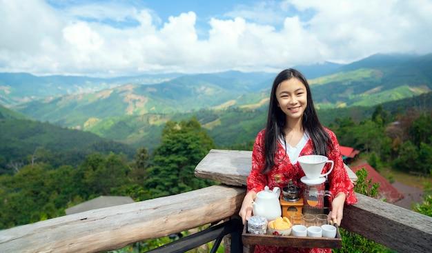 Asiatisches mädchen entspannen mit heißem kaffee und heißem tee, der auf sichtpunkt von doi sakad gesetzt wird