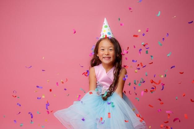 Asiatisches mädchen feiert geburtstagsschläge fängt konfetti auf rosa