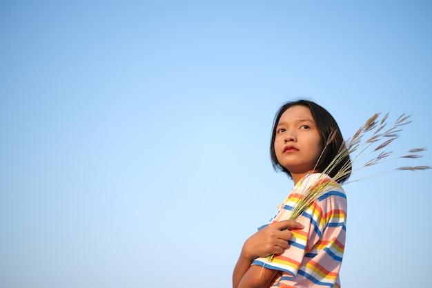 Asiatisches mädchen halten blumengras mit blauem klarem himmel