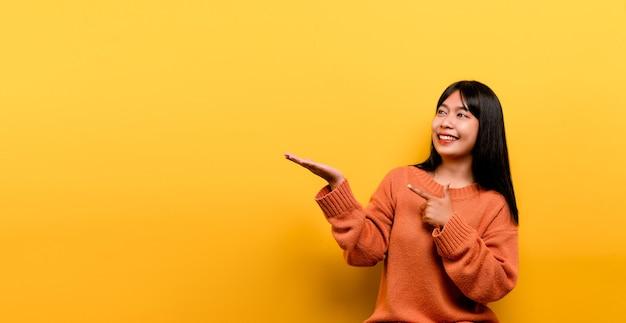 Asiatisches mädchen hübsch, ein orangefarbenes freizeitkleid zu tragen. gelber hintergrund feiern sie den sieg mit einem glücklichen lächeln und dem gesichtsausdruck des gewinners mit erhobener hand. glücklicher ausdruck