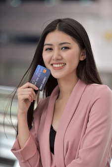 Asiatisches mädchen im rosa anzug schicken sie einer hand, die eine kreditkarte hält, ein süßes lächeln.
