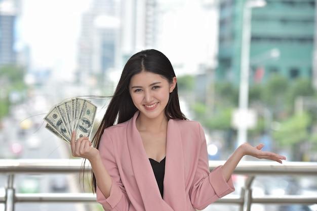 Asiatisches mädchen im rosafarbenen anzug schicken sie einer hand, die ein bargeld hält, ein süßes lächeln.