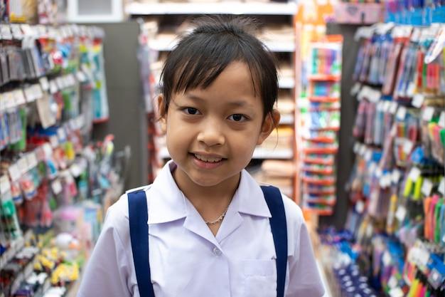 Asiatisches mädchen im schreibwarengeschäft, das stifte und schulmaterial kauft
