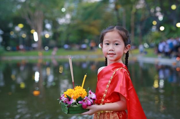 Asiatisches mädchen im thailändischen trachtenkleid mit dem halten von krathong für vergebung göttin ganges.