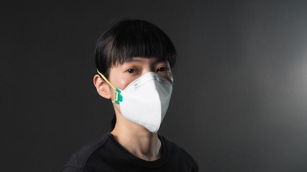 Asiatisches mädchen in einer maske auf schwarzem hintergrund in der coronavirus-quarantäne-situation titel über
