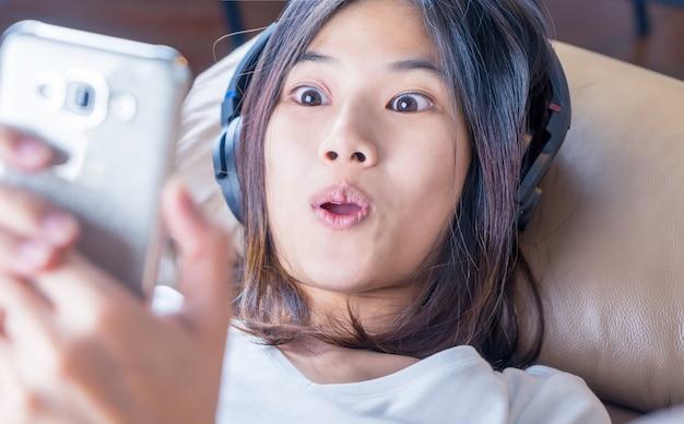 Asiatisches mädchen ist surpisely-schock mit inhalt auf ihrem smartphone