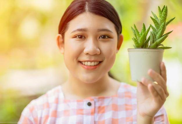 Asiatisches mädchen jugendlich lächelnder griffkaktus-topf, um die erdumwelt zu retten und grünes pflanzenprodukt für gutes gesundheitskonzept zu verwenden.