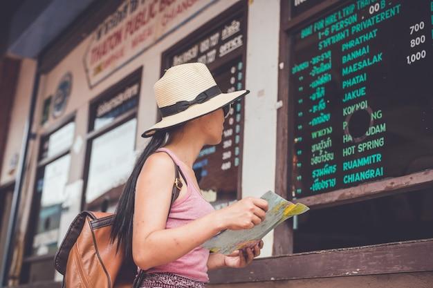 Asiatisches mädchen kauft eine reiseticketleitung, um kreuzfahrtreise zu gehen
