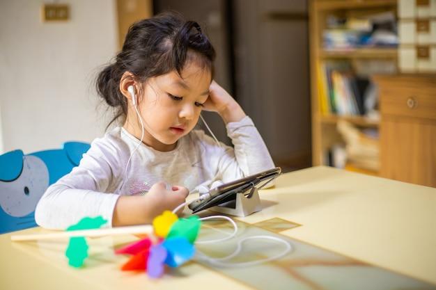 Asiatisches mädchen lernen und studieren online-videoanruf mit lehrer, glückliches mädchen lernen online mit laptop zu hause.