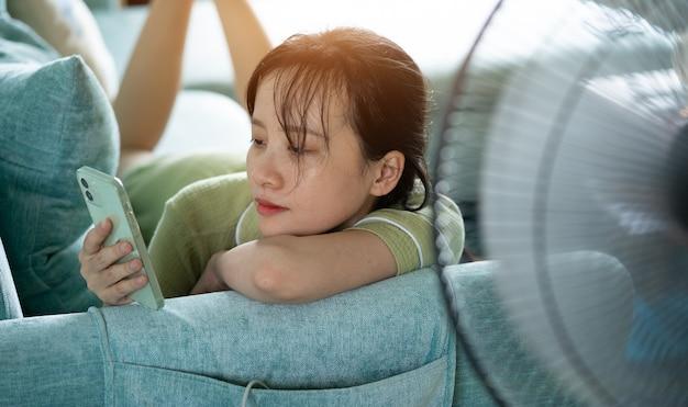 Asiatisches mädchen liegt auf dem sofa und benutzt telefon