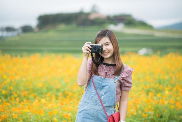 Asiatisches mädchen machen blühende gelbe blumen des fotos, reisekonzept