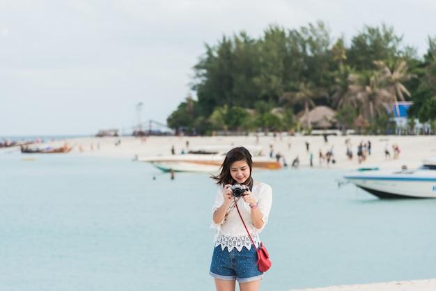 Asiatisches mädchen macht foto auf dem strand